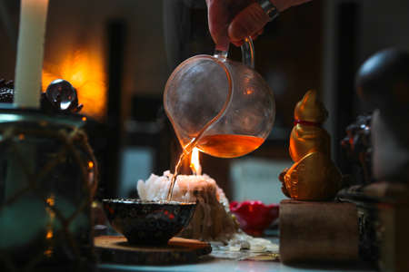 pouring tea from glass teapot into colorful tea bowl on wooden coaster, warm dark atmosphere during tea ceremony Stock Photo