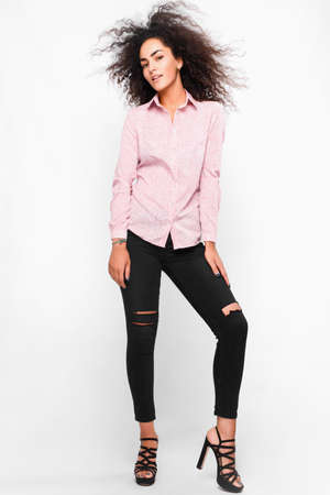 Fashionable portrait of beautiful young woman, wearing black skinny jeans, high heels, pink classic shirt, curly  fuzz hair, smiling, isolated on white background