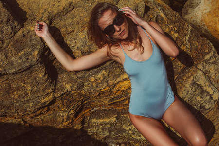 Slim young woman in one-piece blue swimsuit, tanned skin, thin waist, is laying, relaxing, smiling and enjoying on the big yellow sandstones