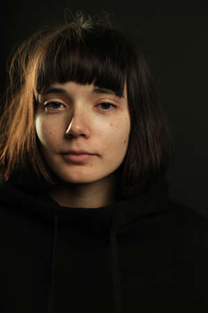 Portrait of young brunette with short hair and bob haircut, straight bang, without make up, calm expression, wearing black hoodie, looking at camera, isolated on black background, space for text