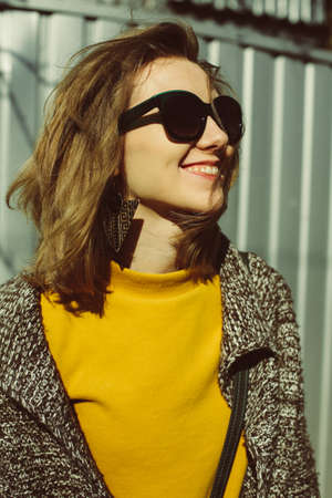 sunny warm portrait of laughing young woman with short fair messy hair, wearing green glasses, yellow blouse, cardigan, outside Stock Photo