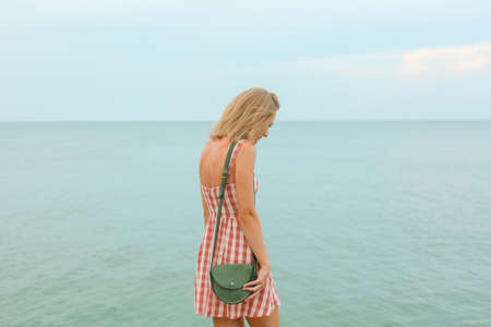 Graceful slim tender woman in red checked short dress and small green leather purse  is looking at the sea, straight horizon line Imagens