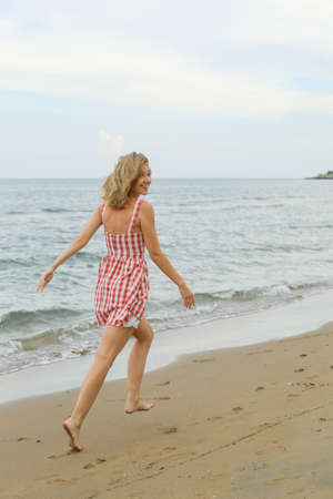 young woman is running along seashore, wearing short red checked dress, looking over shoulder