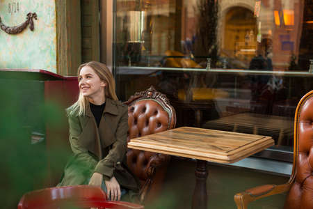 Pretty, positive, smiling, elegant young woman with blond hair, wearing stylish coat is sitting on the terrace of cafe with antique design