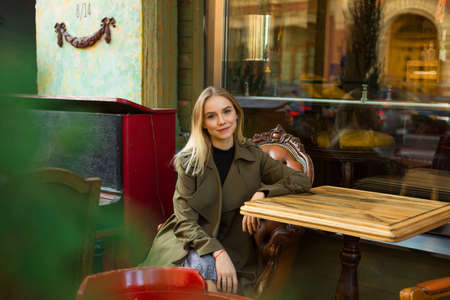 Pretty and elegant young woman with blond hair, wearing stylish coat is sitting on the terrace of cafe with antique design Banco de Imagens