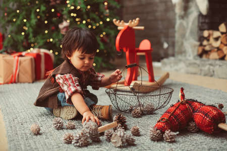 Small boy is sitting on carpet, wearing casual cowboy clothes, checked shirt, vest, jeans, playing with conelet in Christmas interior, red elements, pine cones, Christmas tree Stock Photo