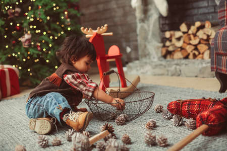 Small boy is sitting on carpet, wearing casual cowboy clothes, checked shirt, vest, jeans, playing with conelet in Christmas interior, red elements, pine cones, Christmas tree