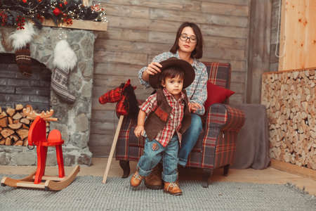 Portrait of mother with small son sitting in checked armchair wearing checked shirts, decorated Scandinavian interior, fireplace