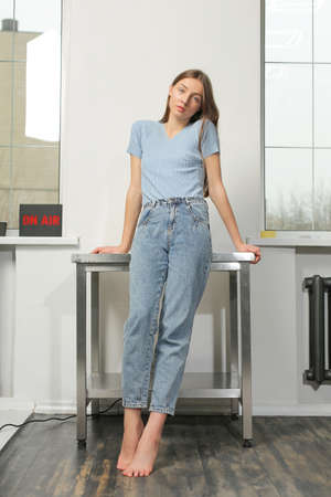 Pretty slim woman with long chestnut hair, wearing blue t-shirt and jeans, is standing, leaning on metal table, near window, white background