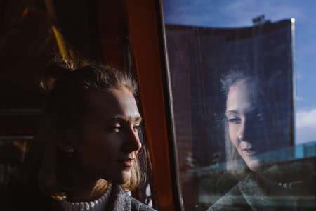 Young smiling woman is watching at the window in public transport, sunny weather, reflection