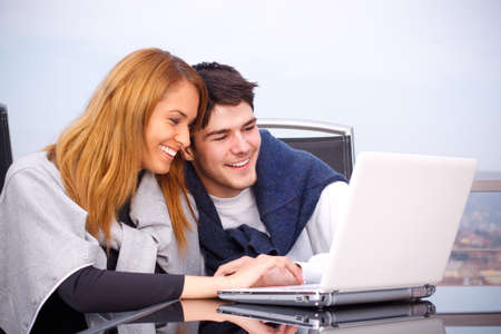 young couple surfing the internet on a laptop photo