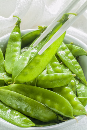 Freshly steamed snow peas served in a white bowl with white chopsticks on a white cloth  photo