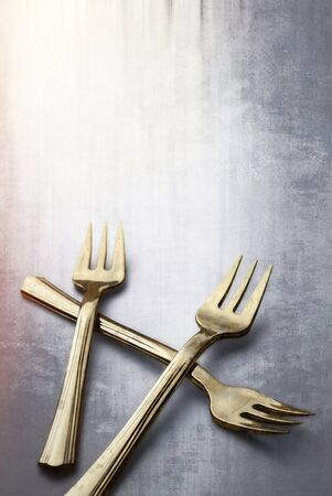 tarnished: Old and Tarnished Gold Forks on textured background with copy space.