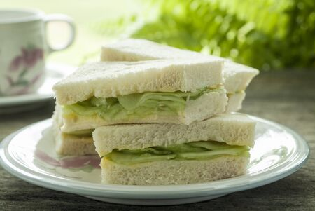 english cucumber: Traditional cucumber sandwiches with a cup of tea.