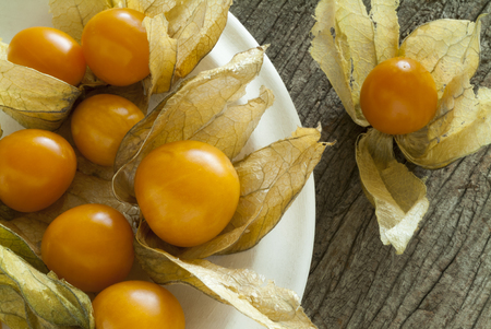 husks: Close up of Golden Berries with husks in a white plate on a rustic wood surface.