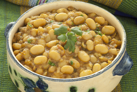 white beans: Close up image of Moroccan stewed white beans served in a painted ceramic bowl.