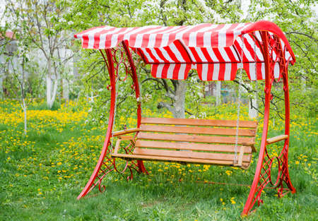 timber bench seat: Swing bench near children house in garden with trees and grass Stock Photo