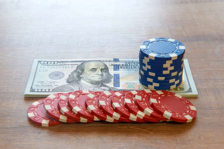 One hundred dollar bills with many poker chips on wooden table