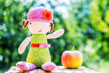 cartoon wood bucket: Plush doll sitting near apple against green trees