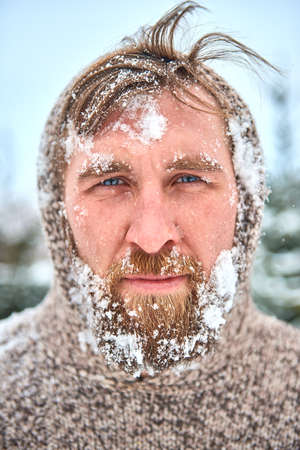 funny bearded man: Portrait of bearded man with snow on his face. Man is frozen in pullover with hood and flying hair. Stock Photo