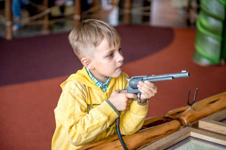 violent: Little boy shooting with revolver gun in amusement park. He is playing