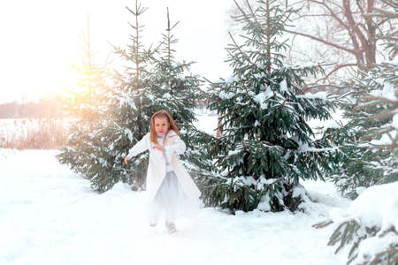 runing: Little girl runing near green fir trees on the snow Stock Photo