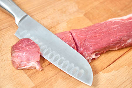 provision: Raw meat slices cutted with knife on the wooden board