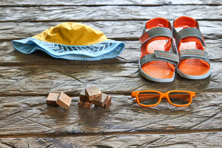 children clothing: Hat,sandal,sunglasses wooden bricks on wood background, summer concept Stock Photo