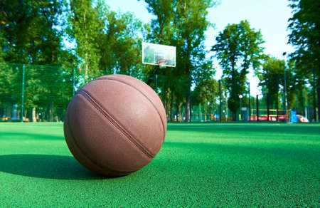 game over: Basketball ball on green field floor against the basket