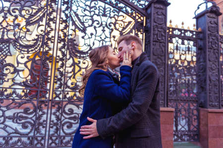 Couple is kissing near the metal gate Stock Photo