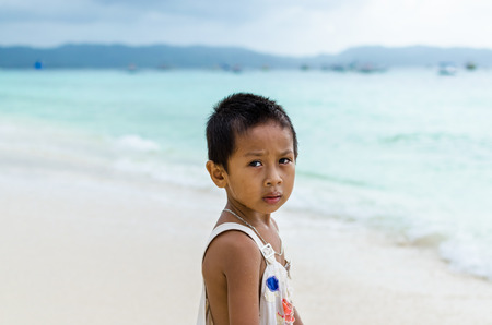 impoverished: Young cute poor Asian boy in a ragged t-shirt from impoverished area with deep thoughtful sight against turquoise sea at tropical white sandy beach on Boracay island, Philippines