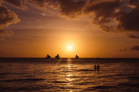 Sailing and fishing boats on the horizon and silhouette of lovely couple walking along tropical exotic white beach with palm trees during beautiful sunset on Boracay, Philippines. photo