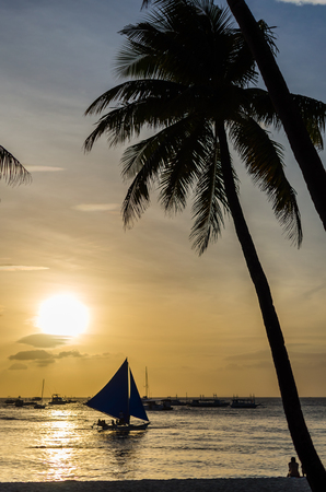 sailingboat: Sailing boat under sail on the horizon and silhouette of people sitting and admiring of beautiful sunset under palm tree at tropical exotic white beach on Boracay, Philippines. Stock Photo