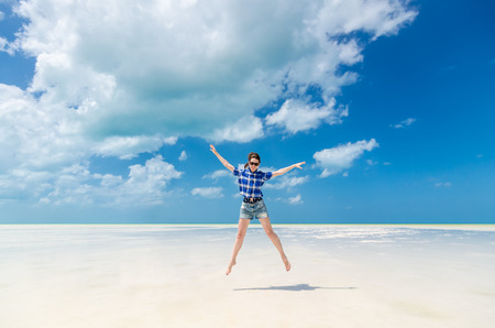 excitement: Beautiful excited cheerful young woman with arms out in blue cotton checked shirt and sunglasses jumping on the background of desert sea lagoon at white sandy beach in the Caribbean sea, Holbox, Mexico