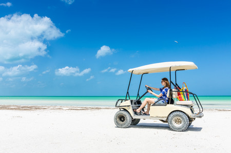 Young adorable woman driving on a golf cart along tropical white sandy beach during her Caribbean vacation on Holbox island, Mexico
