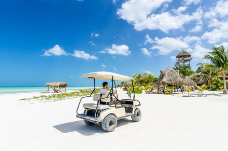 Cute young man driving golf cart along tropical white sandy beach during his Caribbean vacation on Holbox island, Mexico photo