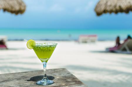 coctel margarita: Fr�o sabroso c�ctel Margarita fresco con lim�n y hielo en una mesa en la playa tropical de arena blanca