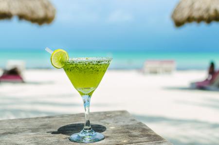 margarita cóctel: Frío sabroso cóctel Margarita fresco con limón y hielo en una mesa en la playa tropical de arena blanca