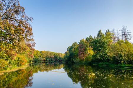 provincial forest parks: Attractive autumn landscape with beautiful woods in red, green and yellow, small wooden bridge on the horizon and great reflection of autumn foliage and trees over lake