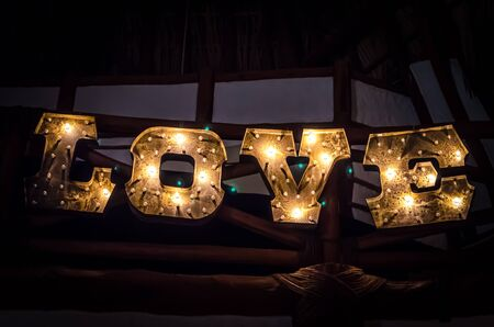 electric bulb: Inscription romantic word Love writing by electric bulb on the wood blackboard outdoors Stock Photo
