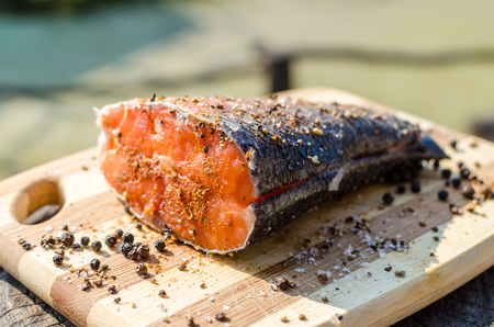 prepared fish: Close up shot of prepared peace of fresh salmon fish outdoors on wooden chopping board rustic style of grilled fish