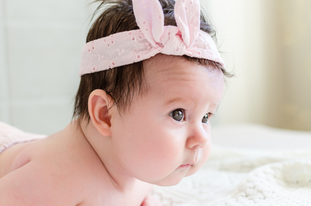 glance: Portrait of cute sweet little newborn baby girl in pink head bandage bow looking with big beautiful hazel brown eyes curious glance photographed sideface. The depth of field is short.
