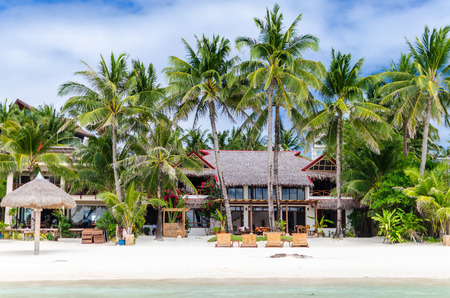 lounges: Luxury tropical villa near the sea with beautiful colourful decor surrounding palm trees and lounges in front of it at famous exotic white sandy beach on Boracay island station 1 Philippines Stock Photo