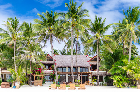lounges: Luxury tropical villa near the sea with beautiful colourful decor surrounding palm trees and lounges in front of it on famous exotic white sandy beach on Boracay island station 1 Philippines