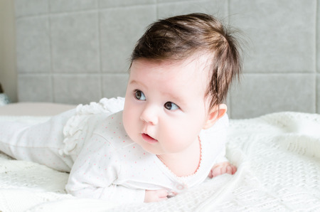 romper: Cute sweet little newborn baby girl with black brunette hair in nice white spotted romper suit looking with big beautiful hazel brown eyes, with opened mouth and lying on white woolen blanket on a bed at home Stock Photo