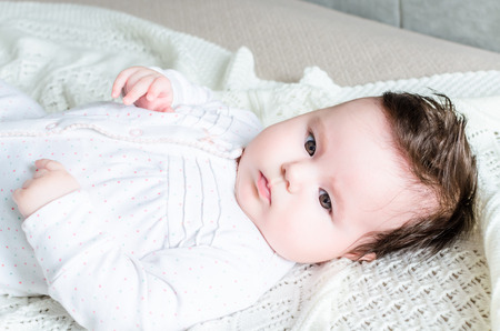 eyes hazel: Cute sweet little newborn baby girl with black brunette hair in nice white spotted romper suit looking with big beautiful hazel brown eyes and lying on white woolen blanket on a bed at home