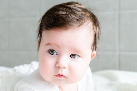romper: Portrait of cute sweet little newborn baby girl with black brunette hair in nice white spotted romper suit looking with big beautiful hazel brown eyes and curious glance on a bed at home