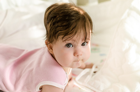 romper: Cute sweet little baby girl with black brunette hair in nice pink romper suit lying on her bed at home and looking at hte camera with smart and curious beautiful hazel brown eyes Stock Photo
