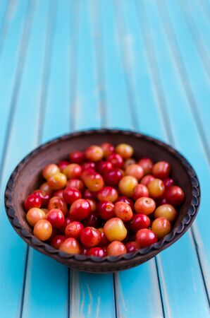?text space?: Ripe juicy sweet cherries in a domestic vintage earthenware bowl on stylized old aged wooden turquoise table background with selective focus. Rustic background with free text space. Foto de archivo