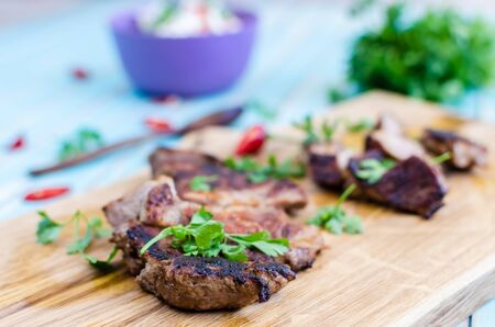 buch: Grilled pork steak cutting in stripes on chopping board close-up served with salad of radishes, cucumbers and fresh goat cheese with red hot chili peppers and buch of green parsley around, wooden spoon over styled wooden turquoise table